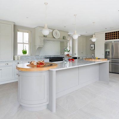 A kitchen filled with grey furniture and walls, completed with CRL Quartz's grey marble-like surface