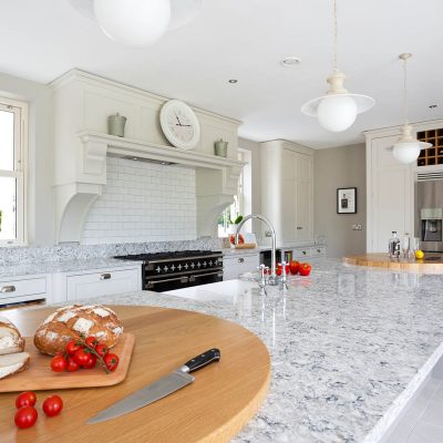 A modern kitchen with CRL Quartz's grey surfaces resembling marble, decorated with speckles